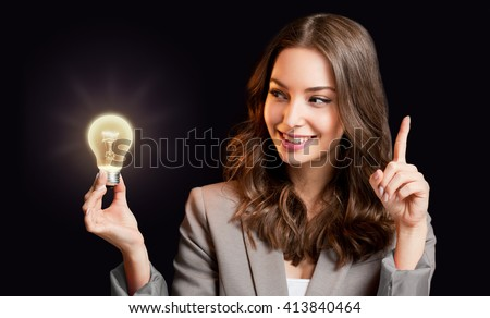 Creative ideas concept, beautiful businesswoman holding glowing symbol. - stock photo