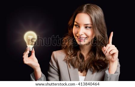 Creative ideas concept, beautiful businesswoman holding glowing symbol. - stock photo