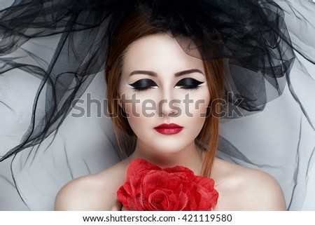 Creative image of a girl in a black veil and a large rose. Beauty portrait of a beautiful young woman lady model, red lips smoky eyes. Professional makeup studio Prepare for party masquerade in Brazil
