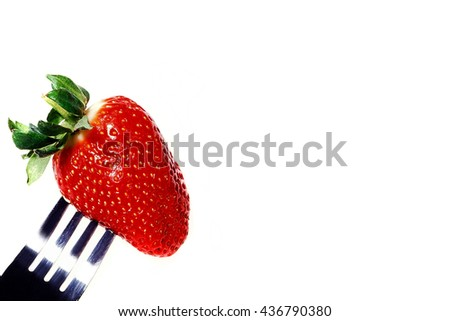 Creative Image of a Single Fresh Strawberry On a Fork Against a White Background With Copy Space - stock photo