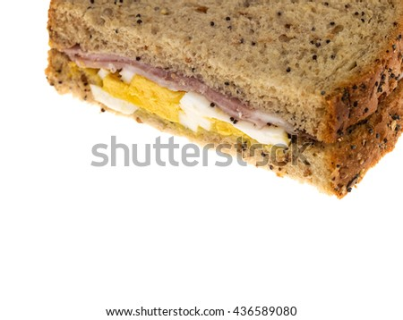 Creative Image of an Egg and Ham Sandwich in Brown Bread Against a White Background with Copy Space - stock photo