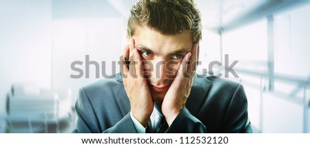 Creative image of attractive male touching his face in trouble - stock photo