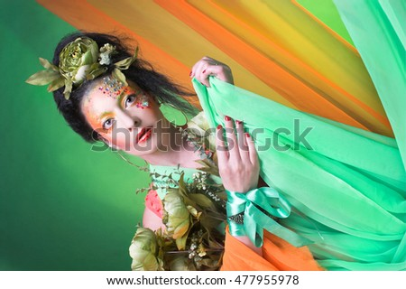 Creative lady. Young brunette with bright flowers and fabric.