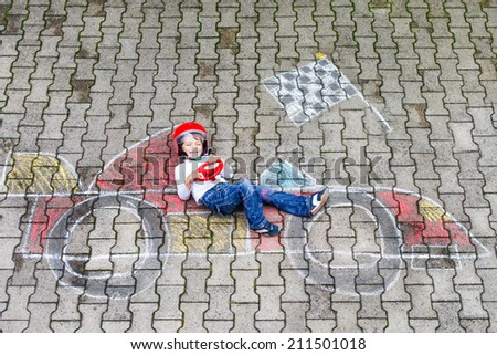 Creative leisure for children: Happy little boy of four years having fun with race care picture drawing with chalk. - stock photo