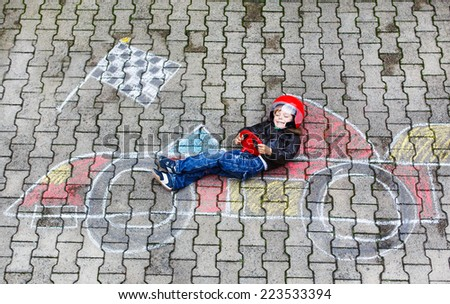 Creative leisure for children: Happy little child of four years having fun with race care picture drawing with chalk. - stock photo