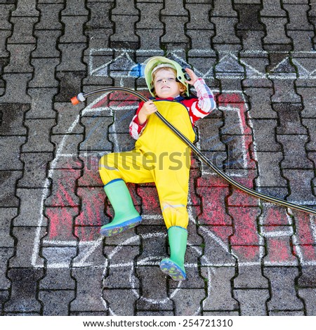 Creative leisure for kids: Funny boy having fun with fire truck picture drawing with chalk, outdoors. Dreaming of future profession. - stock photo