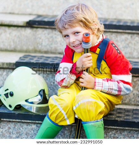 Creative leisure for kids: Funny little child of four years having fun as fireman, in uniform and helmet. Square format. - stock photo