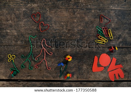 """Creative love story, couple in love, hearts and flowers made from paper clips and thumbtacks on a beautiful wooden background. The word """"Love"""" is written in paper letters. - stock photo"""