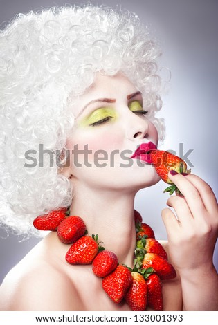 Creative makeup beauty shot of model with strawberries, artistic edit .Woman with strawberry necklace, wig and makeup professionally posing in studio.Beauty with strawberry.