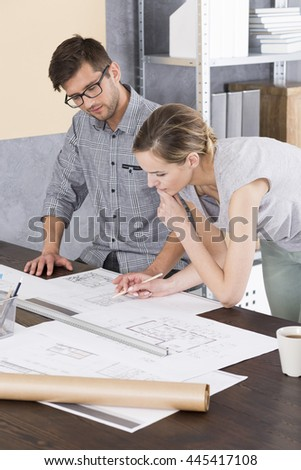 Creative man and woman working together on an architectural project