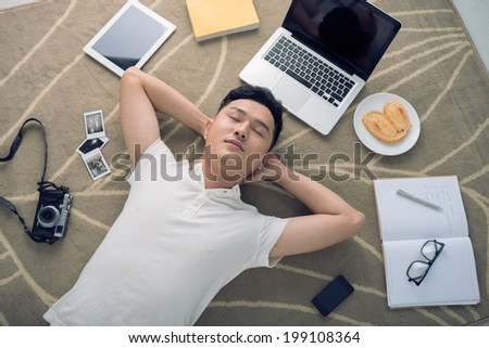 Creative man dreaming while lying next to his favorite things - stock photo