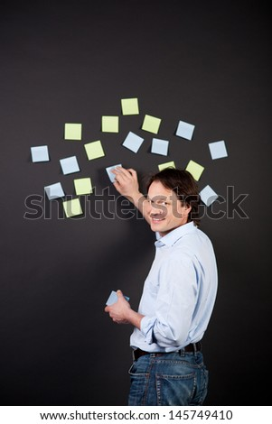creative man working with notes on a black wall - stock photo