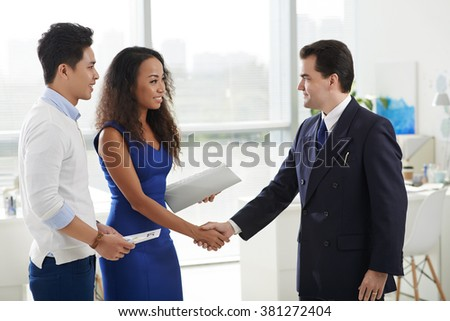 Creative manager shaking hand of client after successful deal