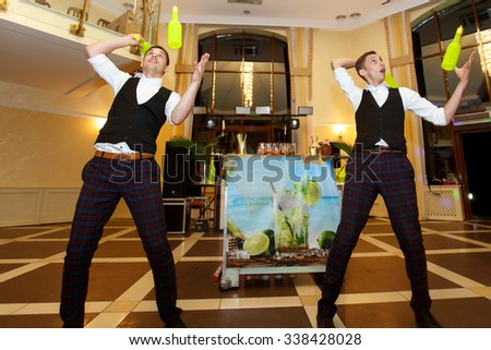 Creative master bartender mixologists juggling bottles and shakers at wedding reception - stock photo
