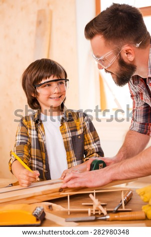 Creative minds at work.Smiling young male carpenter and his son looking at each other while working in workshop - stock photo
