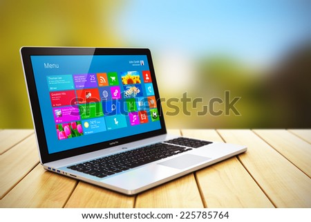 Creative mobile business internet communication and wireless office computer web work concept: modern black glossy laptop or notebook PC with colorful touchscreen interface on wooden table outdoors - stock photo