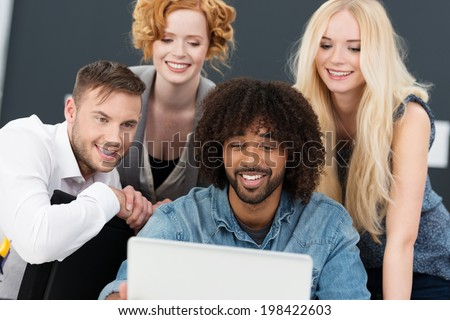 Creative multiethnic young group of business partners working together on a laptop computer grouped around a smiling African American man