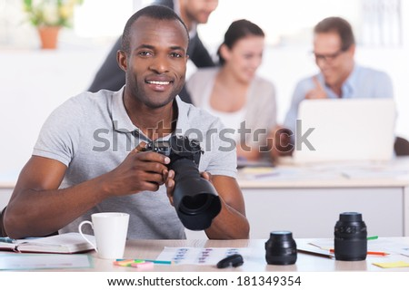 Creative people at work. Handsome young African man holding camera and smiling while three people working on background - stock photo