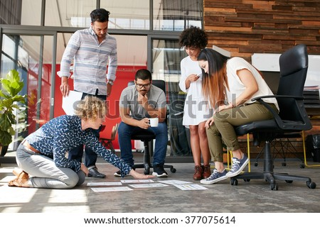 Creative people looking at project plan laid out on floor. Mixed race business associates discussing new project plan in modern office. - stock photo