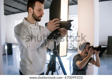 Creative photographers work in studio. Two people with cameras during the studio session. Creative photo and video team shooting in interior