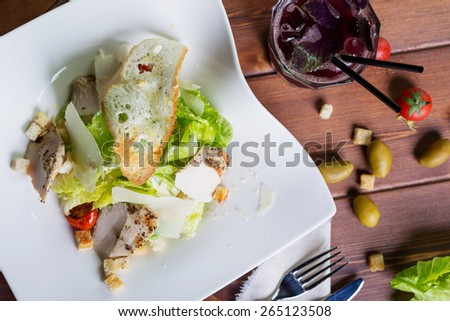 creative photography delicious Caesar salad with slices of chicken breast, parmesan, lettuce and croutons on a white plate on a wooden table in a restaurant with decor