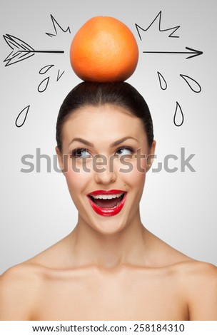 Creative portrait of a beautiful smiling woman holding a red grapefruit pierced with a sketchy arrow on her head. - stock photo