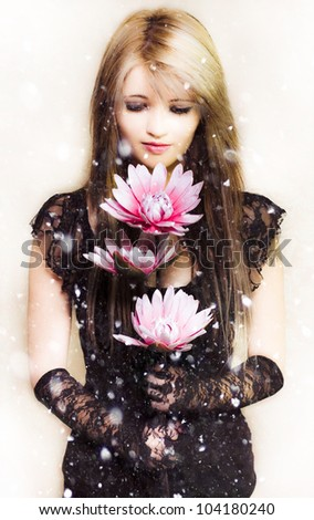 Creative portrait of a beautiful young woman in elegant fashion holding a delicate flower in the falling snow of winter - stock photo