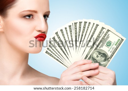 Creative portrait of a nude girl with beautiful face and body holding hand fan made of 100-dollar currency banknotes on blue background. - stock photo