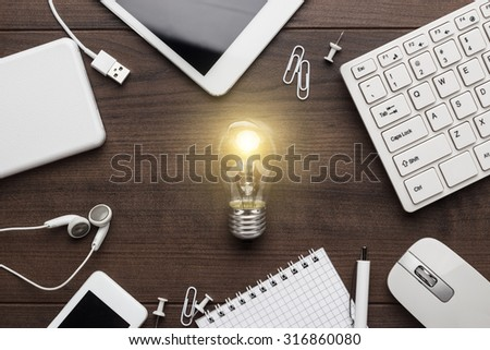 creative process concept with different gadgets and office stationery on the wooden table - stock photo