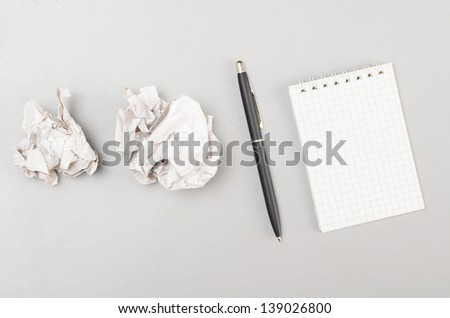creative process. crumpled wads and blank notebook - stock photo