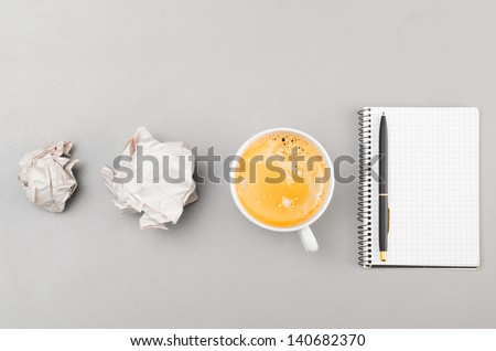 creative process. crumpled wads, notebook and cup on gray - stock photo