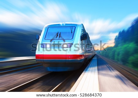 Creative railroad travel and railway tourism transportation industrial concept: scenic summer view of moving modern high speed streamlined passenger commuter train on tracks with motion blur effect