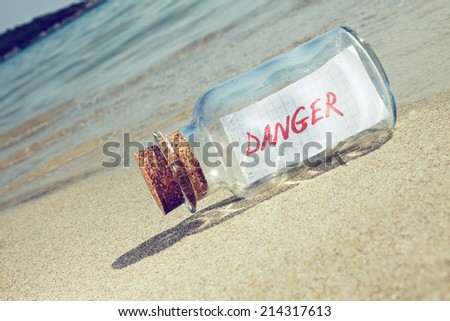 Creative safety and danger concept.  Bottle with a message on beach
