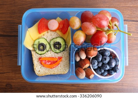 Creative sandwich with fruits and nuts in lunchbox on wooden background - stock photo