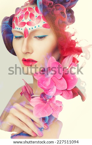 Creative shoot. Beautiful fashion woman With Conceptual Creative Makeup With Dispersion Effect - stock photo