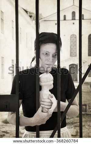 creative slightly textured image of sad woman holing a broken doll behind a looked gate. - stock photo