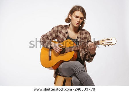 Creative soul. Handsome young guitar player playing acoustic guitar while sitting against white background - stock photo