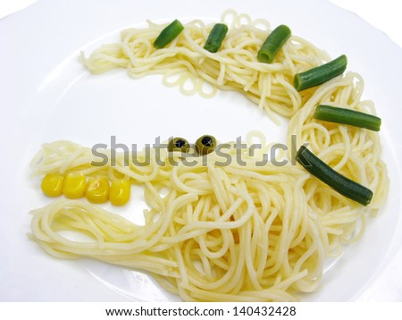 creative spaghetti food garnish with sausage crocodile shape - stock photo