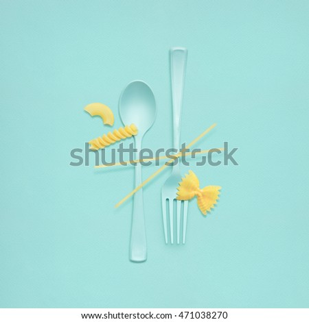 Creative still life of fork and spoon at a lunchtime with raw pasta served.