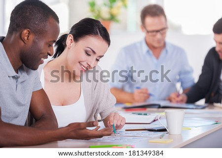 Creative team at work. Two business people sitting together at the table and discussing something while other people working on background - stock photo