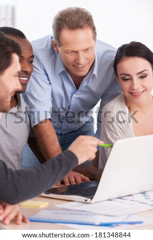 Creative team brainstorming. Group of business people in casual wear sitting together at the table and discussing something while looking at the laptop - stock photo