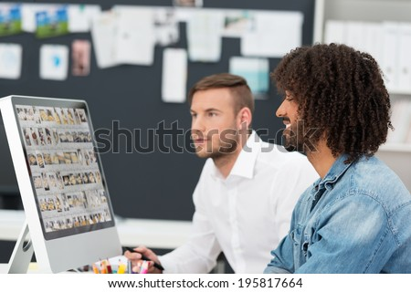 Creative team editing a photo shoot with a young trendy African American man and a male coworker working on a computer monitor together - stock photo