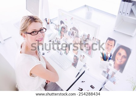 Creative team going over contact sheets in meeting against business people - stock photo
