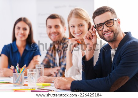Creative team. Group of confident business people in smart casual wear sitting at the table together and smiling  - stock photo