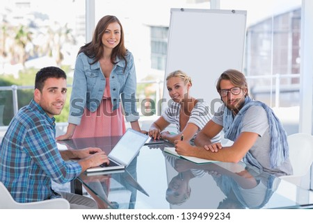 Creative team having meeting and smiling at camera in bright office - stock photo
