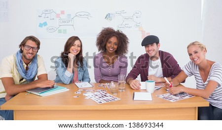Creative team smiling at camera sitting at large desk in office - stock photo