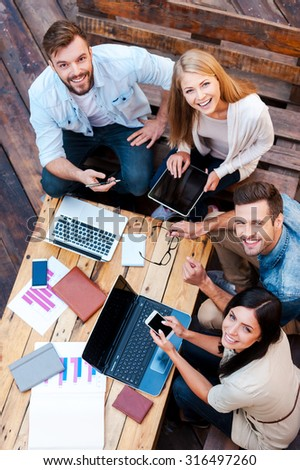 Creative team. Top view of four young people working together and looking at camera while sitting outdoors - stock photo