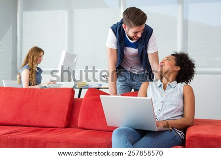 Creative team using laptop on sofa in the office - stock photo