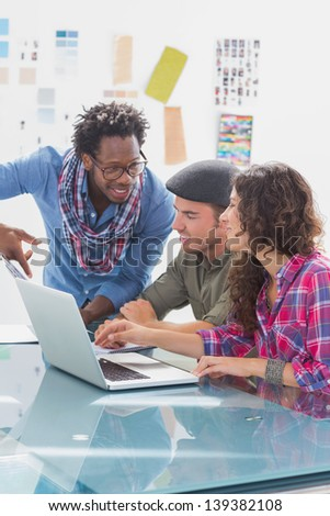 Creative team working together on laptop at desk in office - stock photo