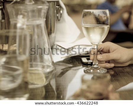 Creative Toned monochrome Images of a Man Holding A Glass of White Wine on a Table Outside - stock photo